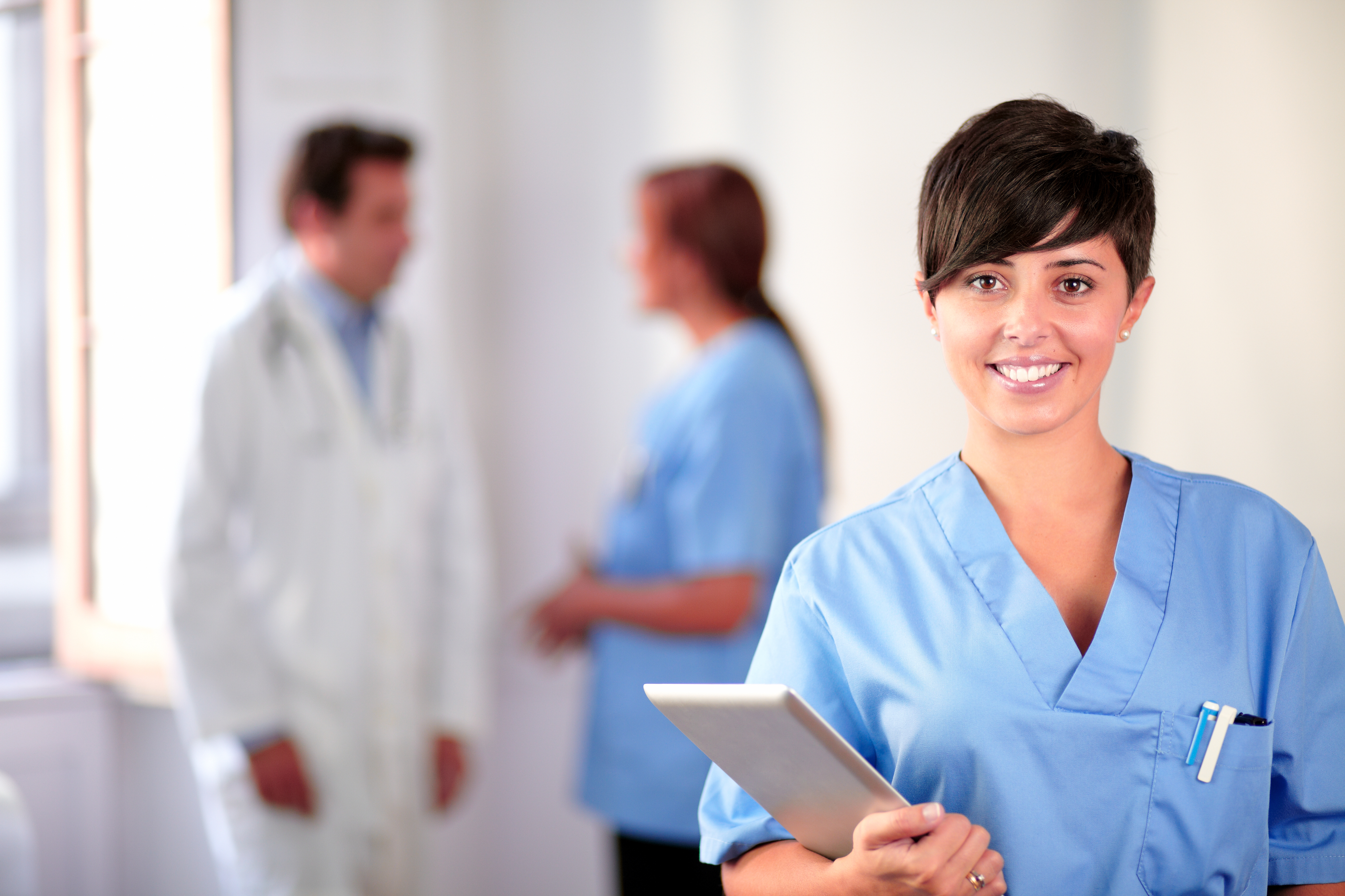 Portrait of a lovely latin nurse on blue uniform standing and smiling on medical team background